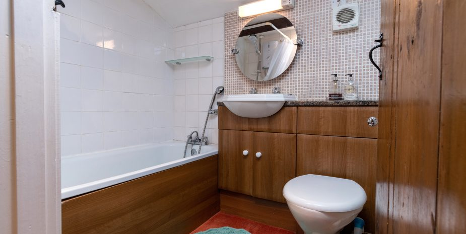 Bathroom with shower over bath (note, low ceiling height in shower for tall people!)
